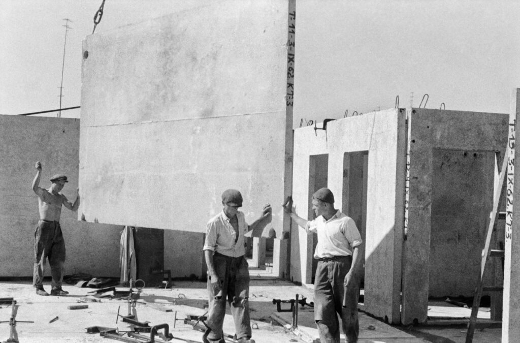 Workers place a prefabricated slab on the building's storey, which is fed to them by a crane.