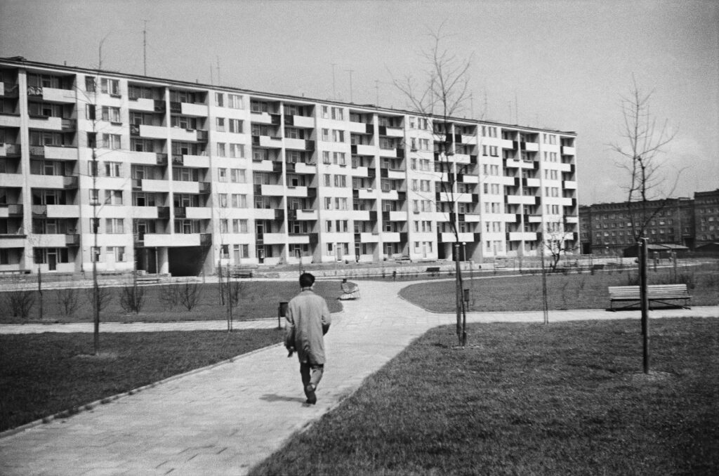 A man in a coat marches down the sidewalk toward a wide seven-story block.