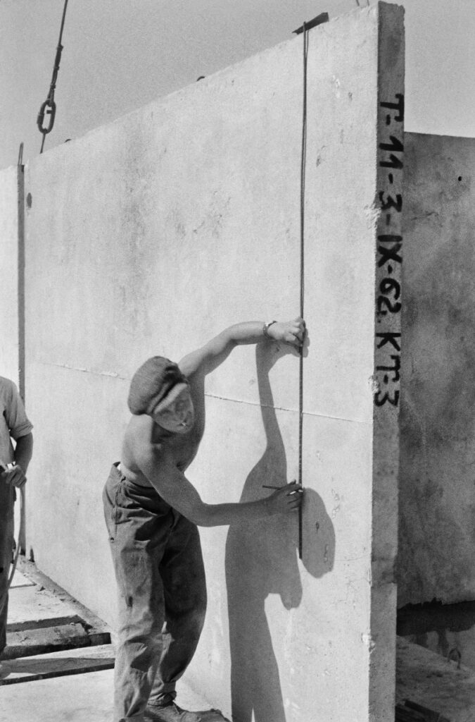 A shirtless worker in a flat cap places a prefabricated slab fed to him by a crane on the building's storey