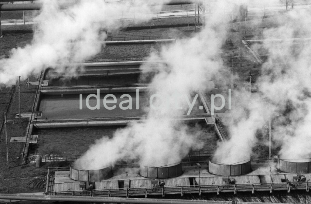 A view from above on the roof of the factory hall from which smoke is escaping from wide chimneys.