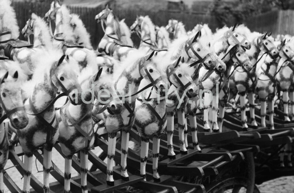 The shot shows a row of wooden rocking horses painted white.