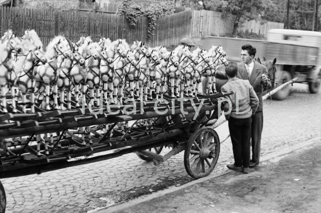 The shot shows a row of wooden, white-painted rocking horses placed on a wooden horse-drawn cart. On the right, an agent standing next to the workhorse is talking to a passerby.
