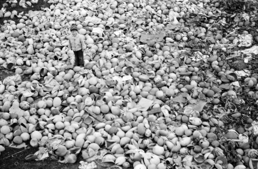 A child in the middle of a pile of broken balls.