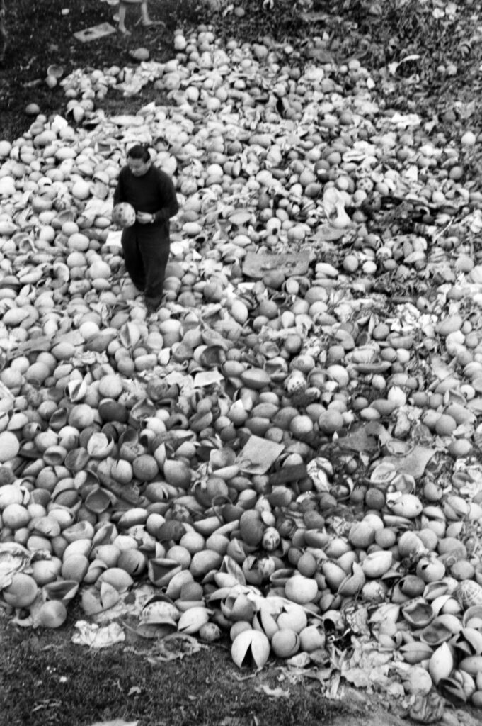 A man with a ball in his hand in the center of a pile of broken balls. pile of broken balls.