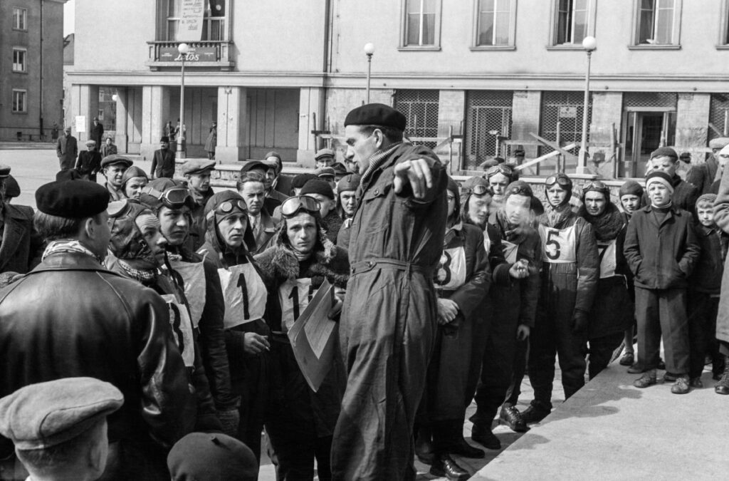 A man in a jumpsuit, standing on a platform, explains something, gesturing to the players gathered in front of him.
