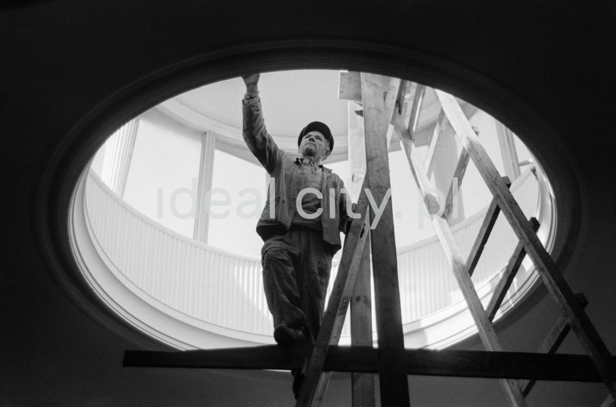 A man in work clothes, standing on a ladder, performs finishing works inside a circular skylight located in the ceiling of the building.