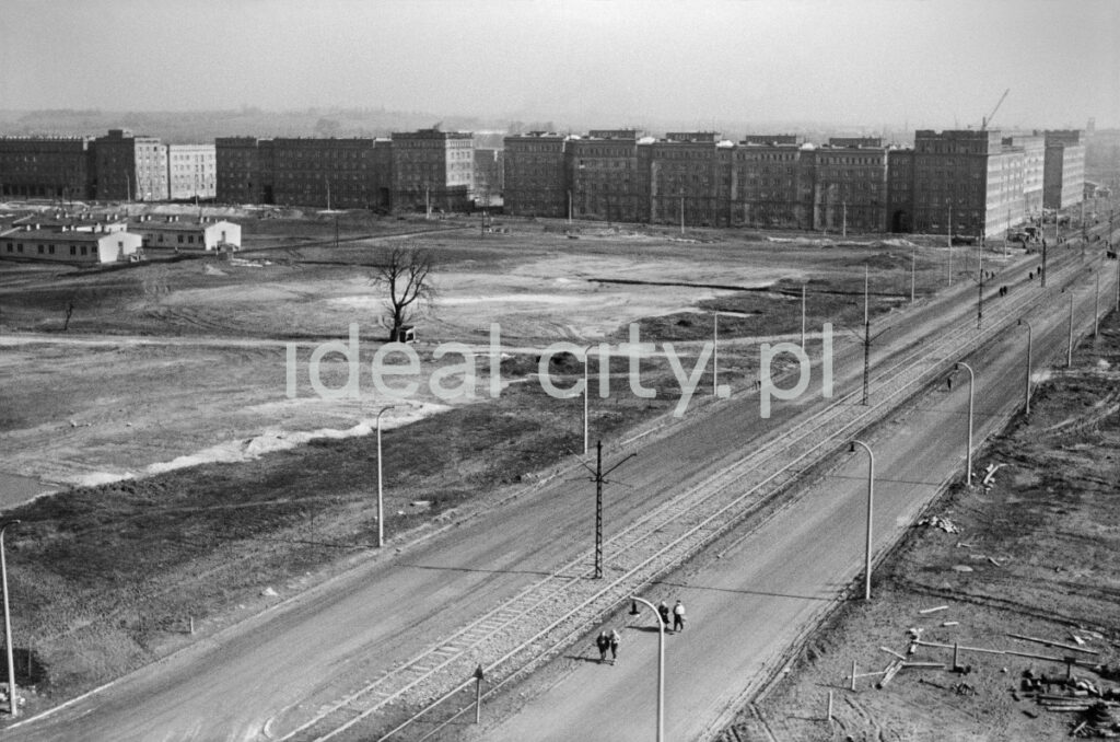 A view from above on the newly created two-lane road with a tramway, on the left an empty, unpaved square, compact buildings in the perspective.