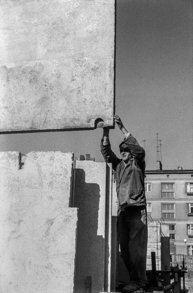 A man in work clothes steers a concrete slab fed by a crane.