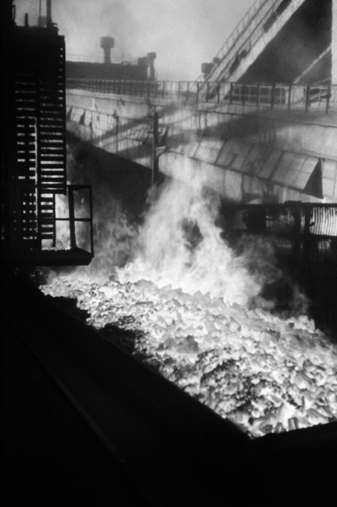 Vertical view of a burning coke heap between the constructions of the plant.
