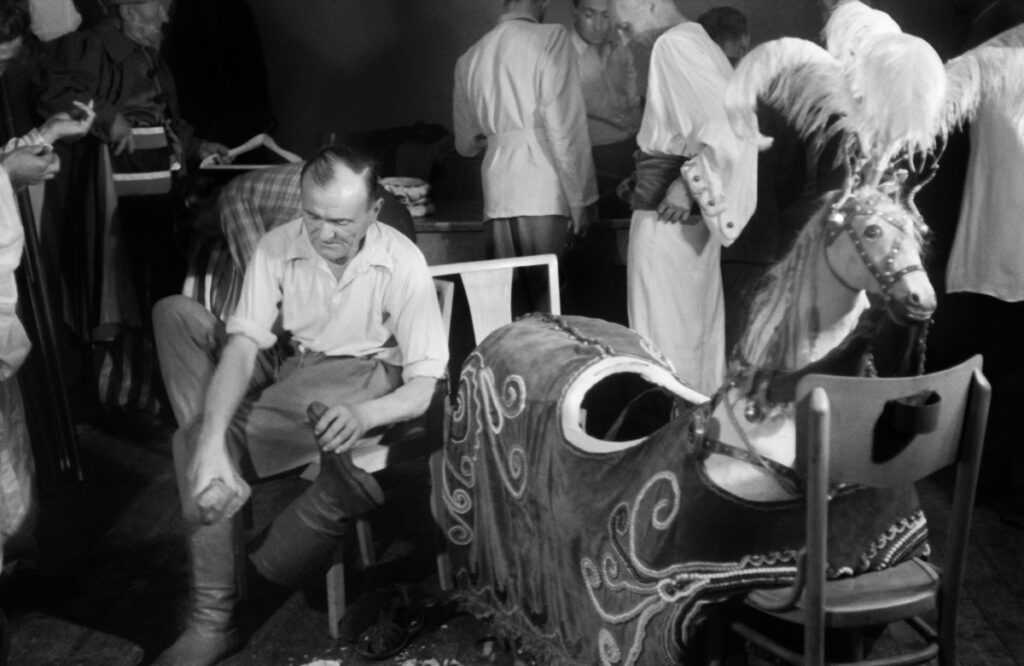 A man in a shirt, while sitting, wears boots with high uppers, next to a horse outfit with a headpiece.