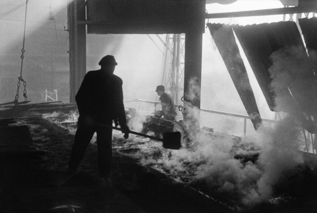 Two men in work clothes are operating shovels over the smoking substance in the production hall.