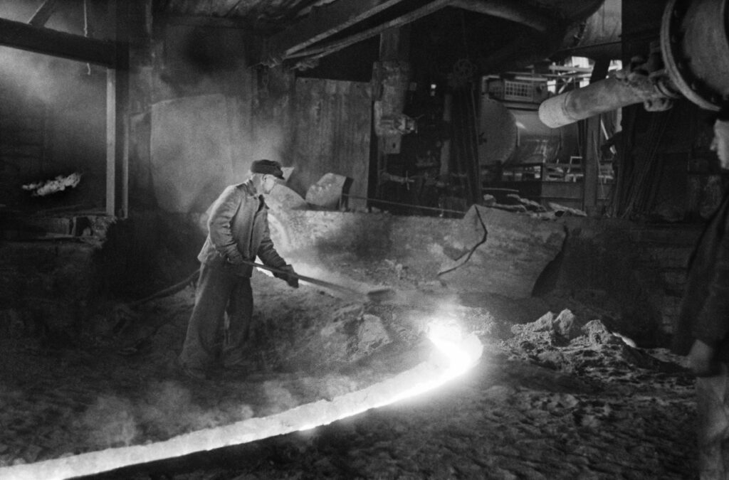 A man in work clothes uses a shovel to correct a stream of flowing iron.