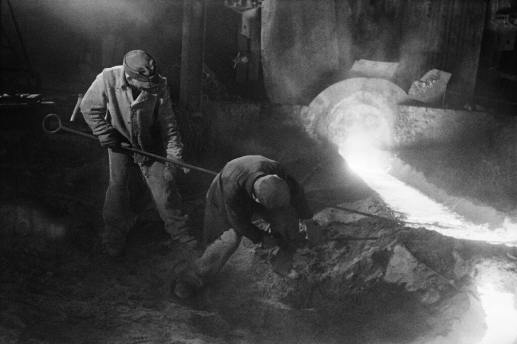 Two men in working clothes use long rods to correct a stream of flowing iron.