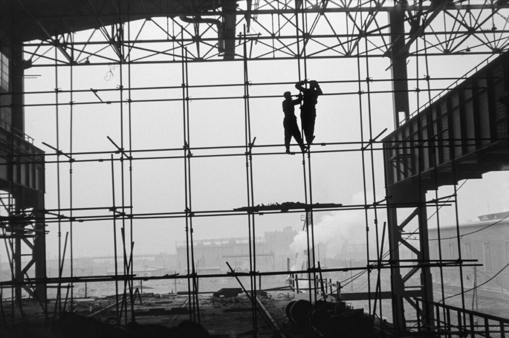 Silhouettes of two men in work clothes on scaffolding along the wall of a newly built hall, factory landscape in the background.