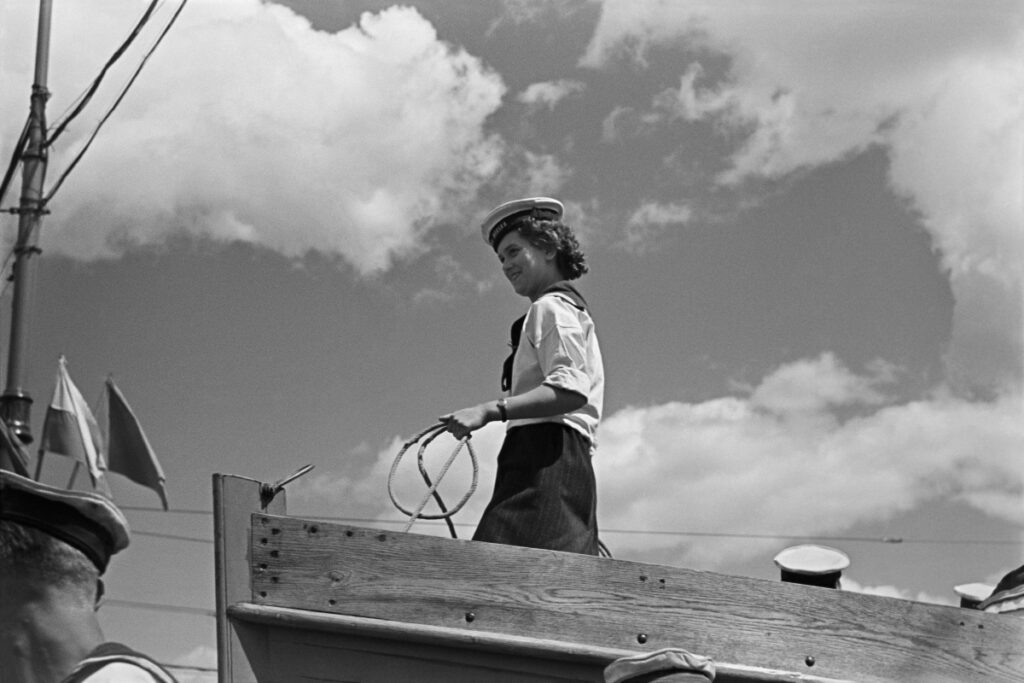 A young woman in a sailor suit stands at the front of the boat holding a rope in her hand.