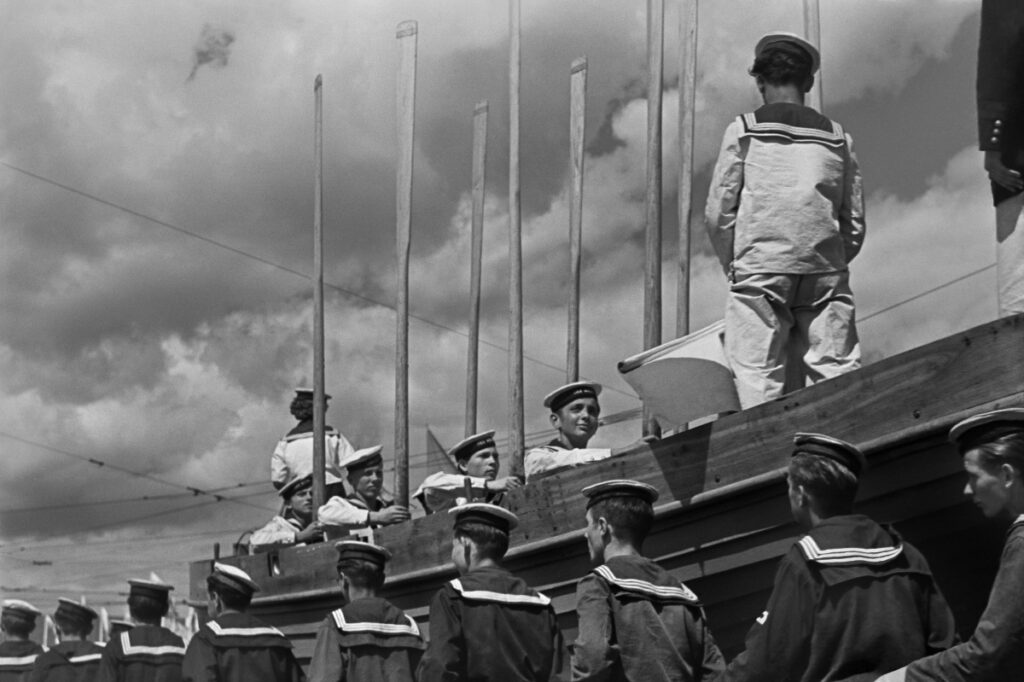 Young men in sailor's outfits stand with their oars upright in a wooden boat placed on a raised platform, below are others marching along the side.