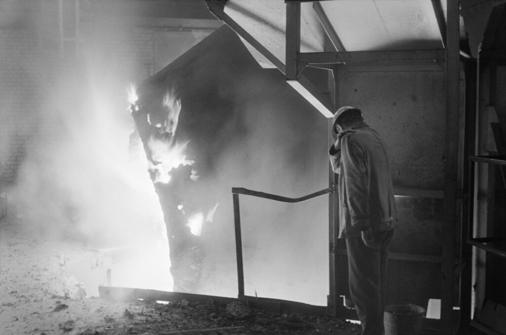 A man in work clothes and a helmet on his head is standing on the dais watching the fire bursting below.