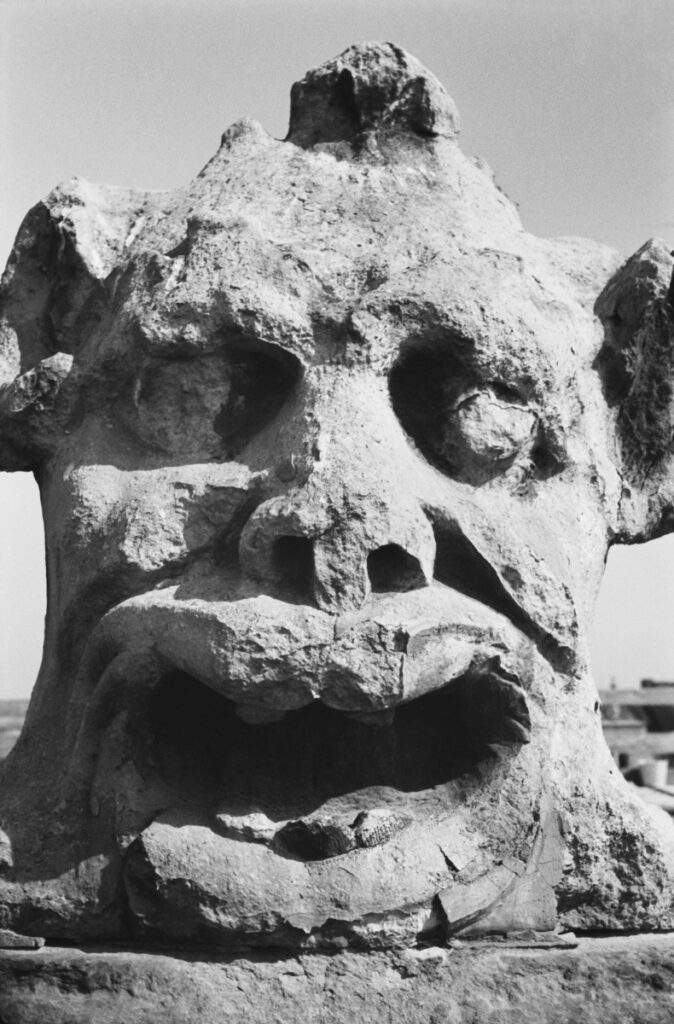A portrait close-up of a mascaron face made of sandstone.