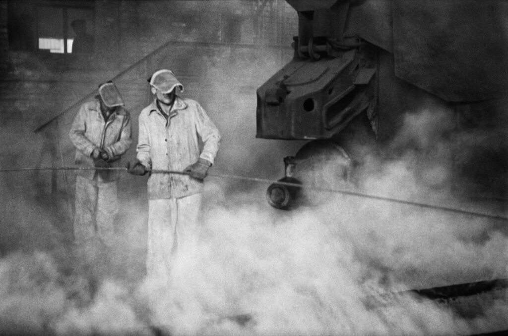 Two men in metallurgical clothes hammer a long rod into the foundations of a huge, steaming structure.