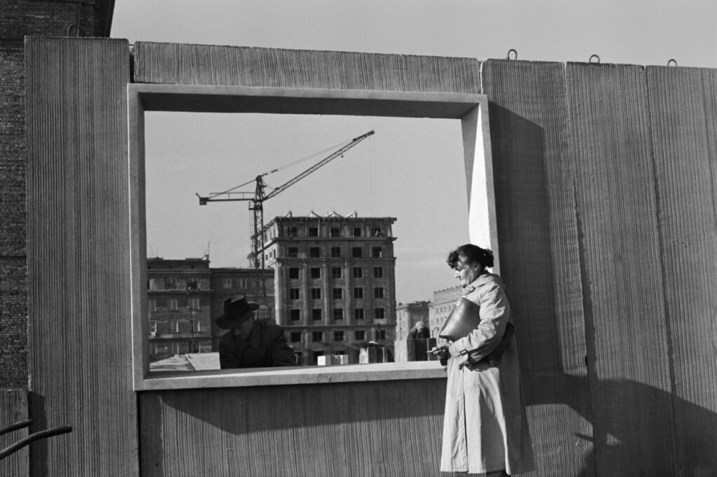 A woman in a coat, with a briefcase at hand, examines the prefabricated window wall of the building. In the background, apartment blocks and a construction crane.
