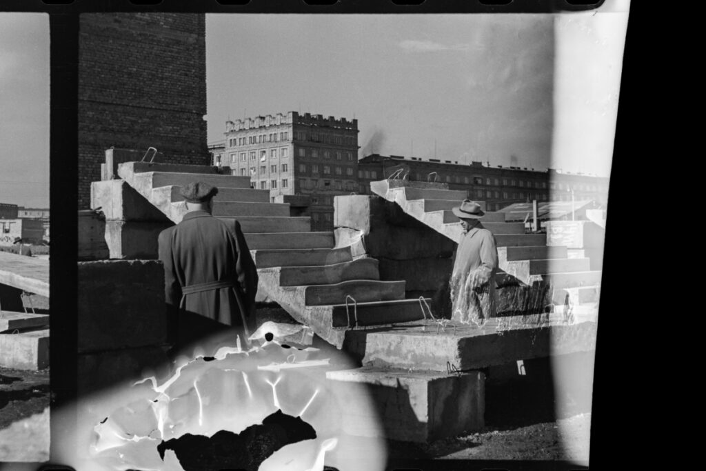 Men in coats and hats look at the display of prefabricated stairs. In the background, apartment blocks. Negative damaged while developing or burnt.
