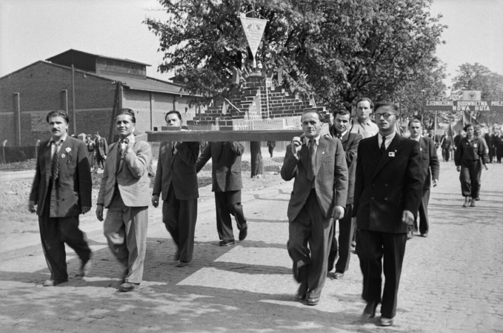 Men in suits march down the street, carrying a model of a pyramidal brick structure on their shoulders.