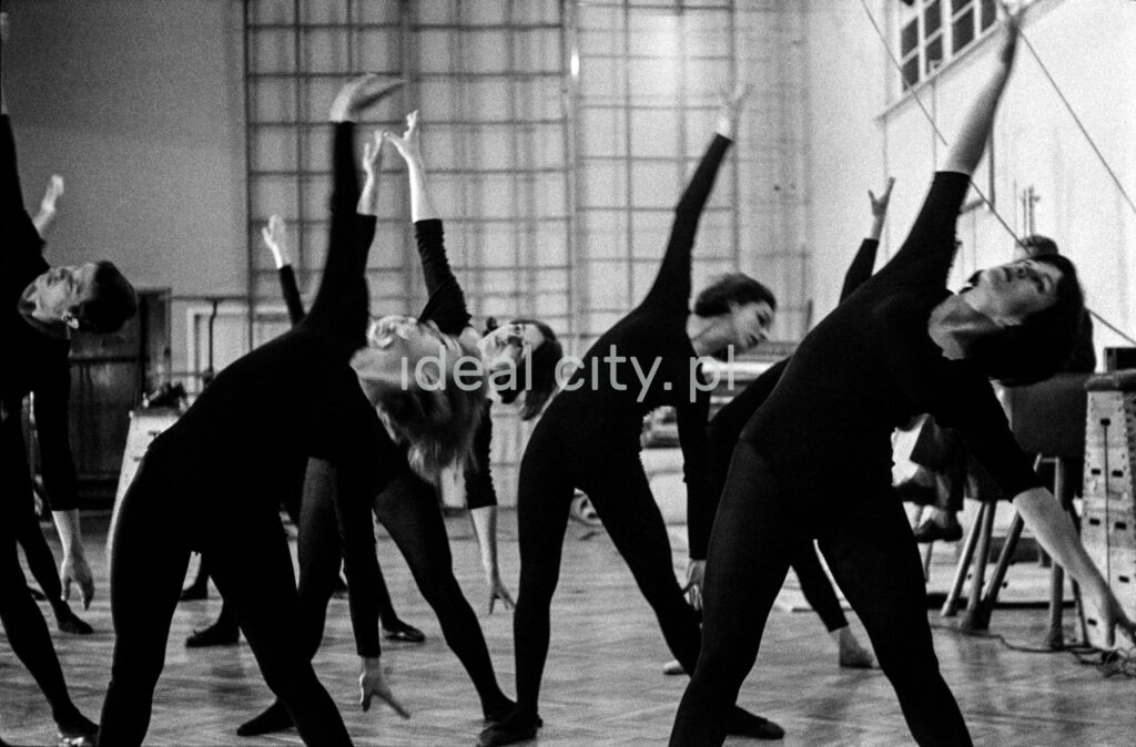 Dancers in black tight costumes lean to the left, lifting their right arms up.