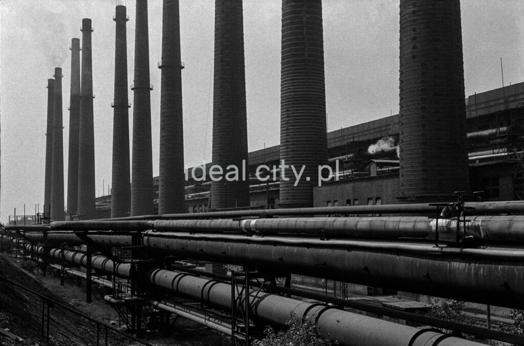 A shot of a series of successive high chimneys. On the right, a factory hall.