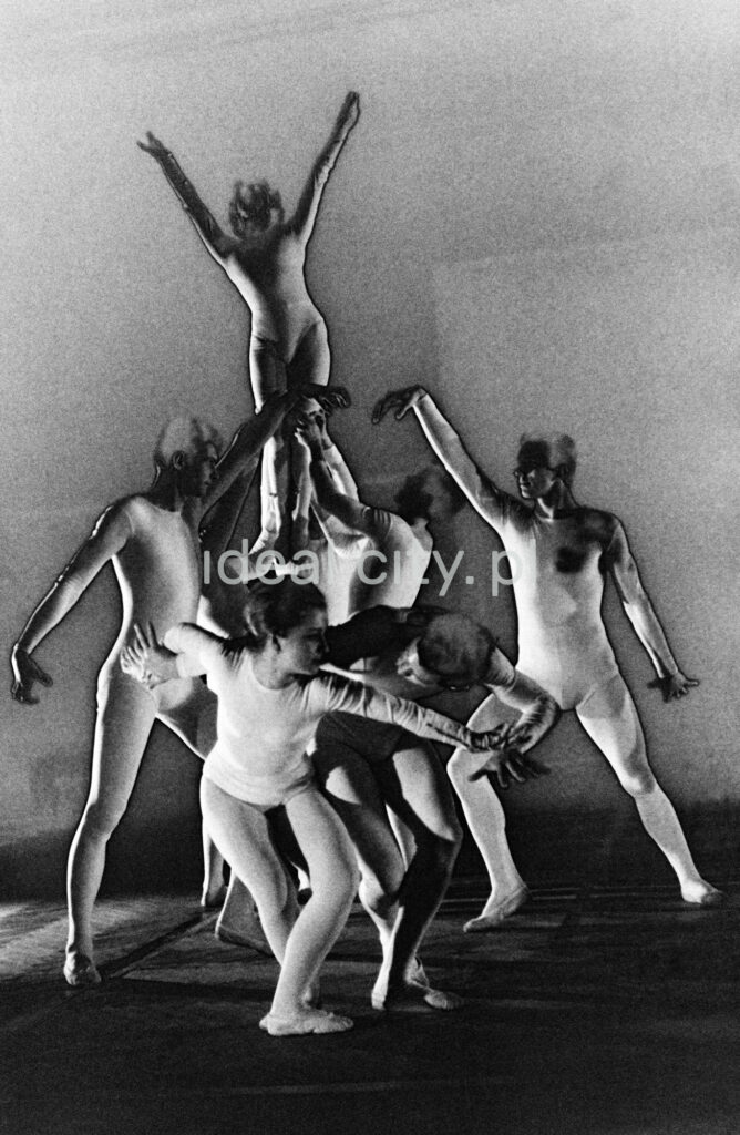 A group of dancers in tight-fitting costumes perform a collective figure on stage with a black background. The negative was solarized.