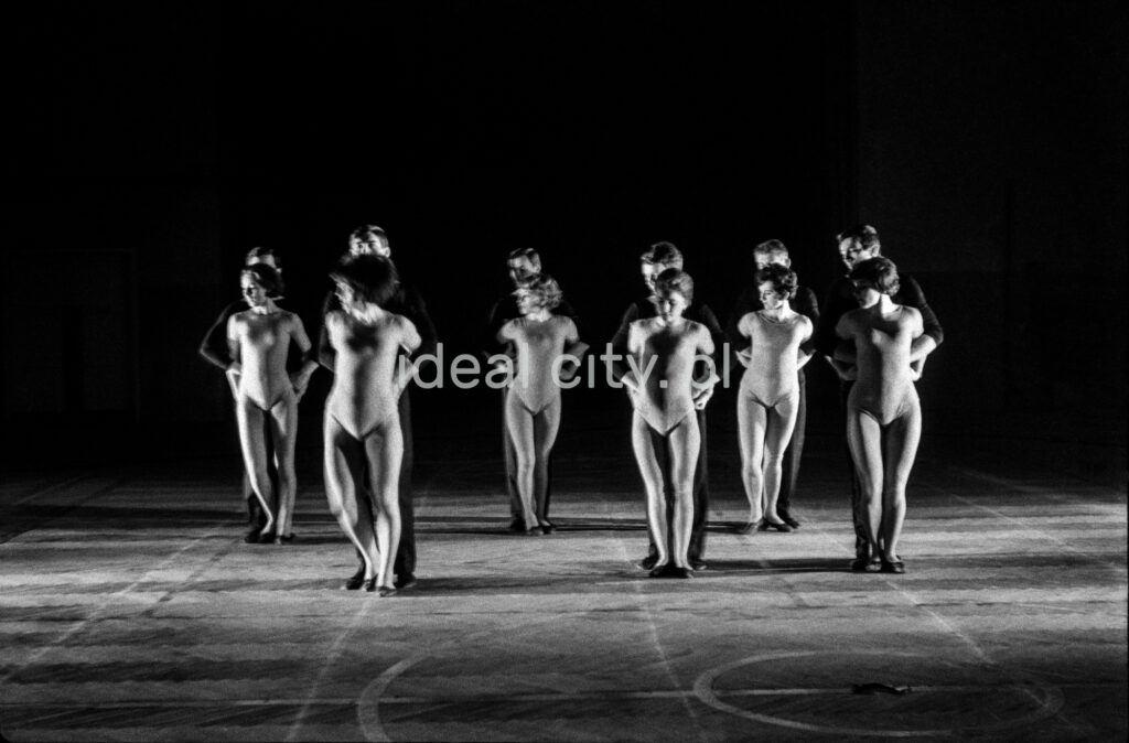 A group of dancers in tight-fitting costumes perform a collective figure on stage with a black background.
