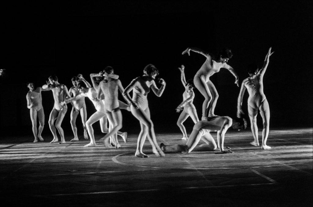 Tancerze w białych, obisłych strojach wykonują zbiorowe figury taneczne