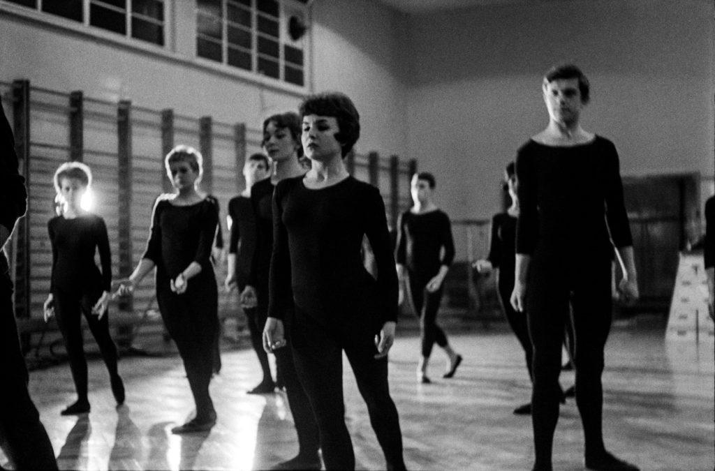 Tancerze w czarnych, obisłych strojach wykonują zbiorowe figury taneczne