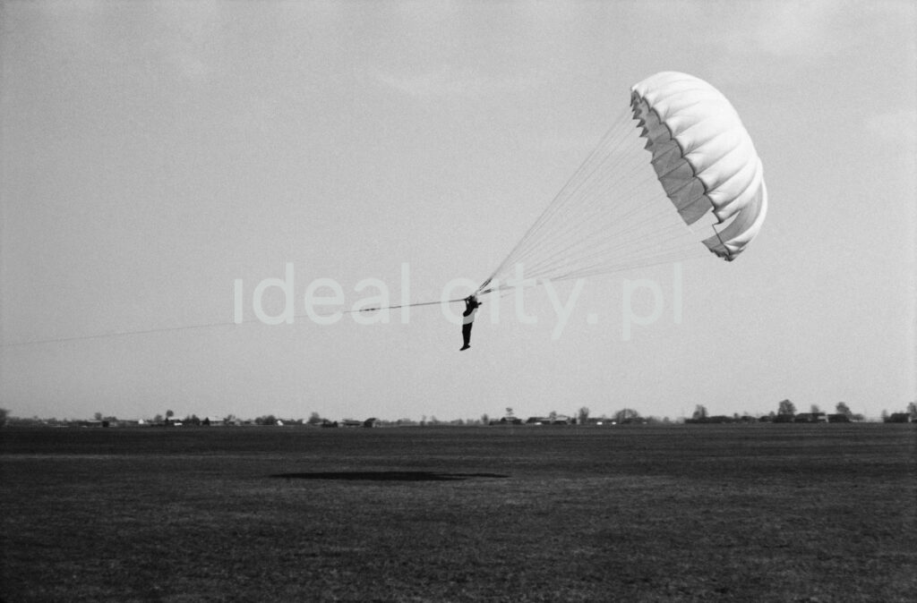 The paratrooper with the taut parachute rises at an angle, tethered just above the ground.