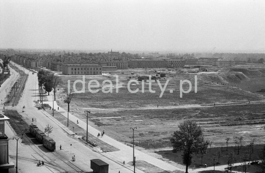 A view from above on a wide avenue with tram traffic, on the right meadow areas, housing development in perspective.