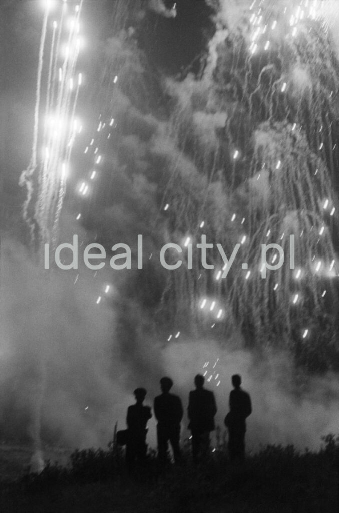 Four figures in uniform watch the fireworks in the sky.
