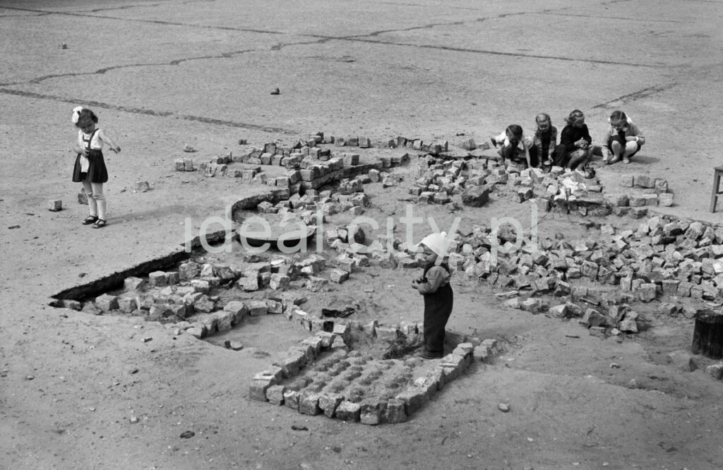 Children play with paving stones in an unfinished city square.