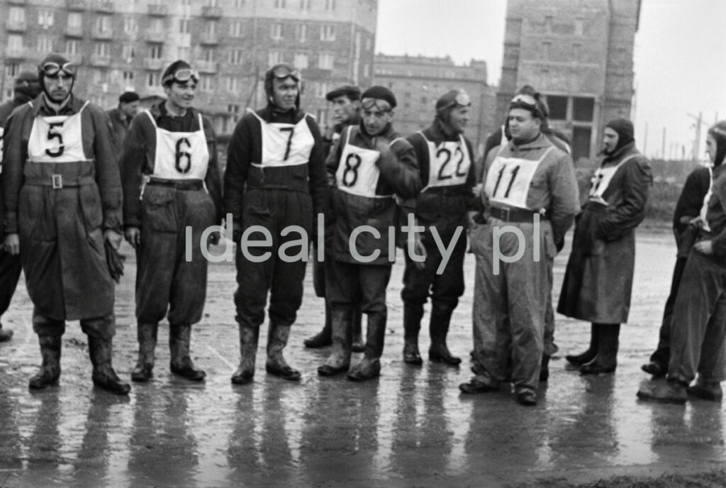 Motorcyclists with numbers on their chests are standing on wet asphalt. Block buildings in the background.