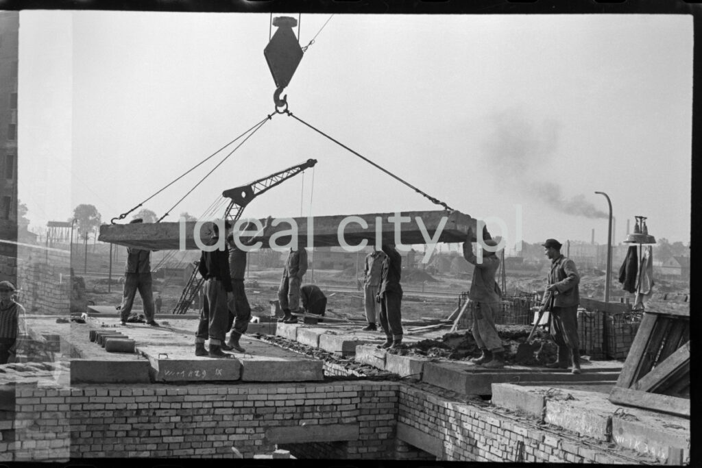 Workers pick up a prefabricated concrete slab fed to them by a crane.