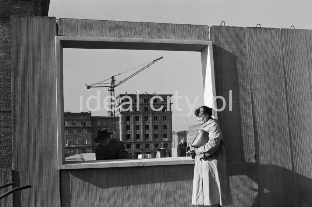 A woman in a coat, with a briefcase under her arm, stands at the window opening of the prefabricated wall. Residential buildings in the background.