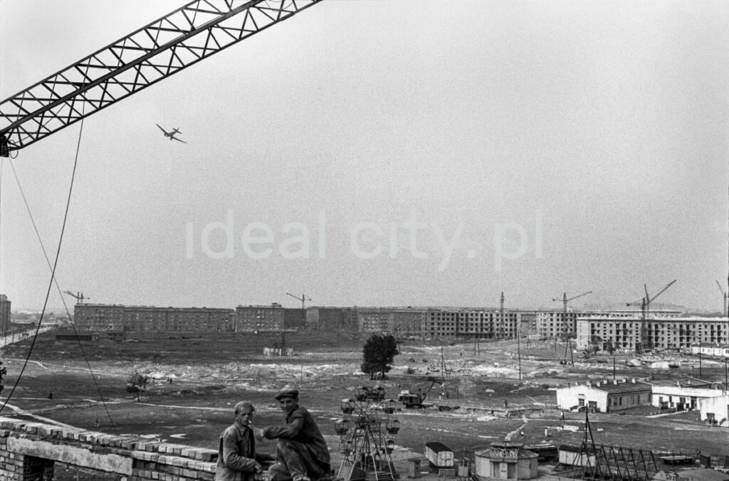 View of the city under construction. In the foreground, there are two small silhouettes of workers, a plane is flying in the sky.