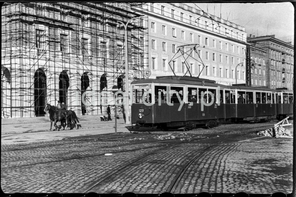 A tram passes in front of a monumental residential building covered with scaffolding, two men are riding on the paving next to it.