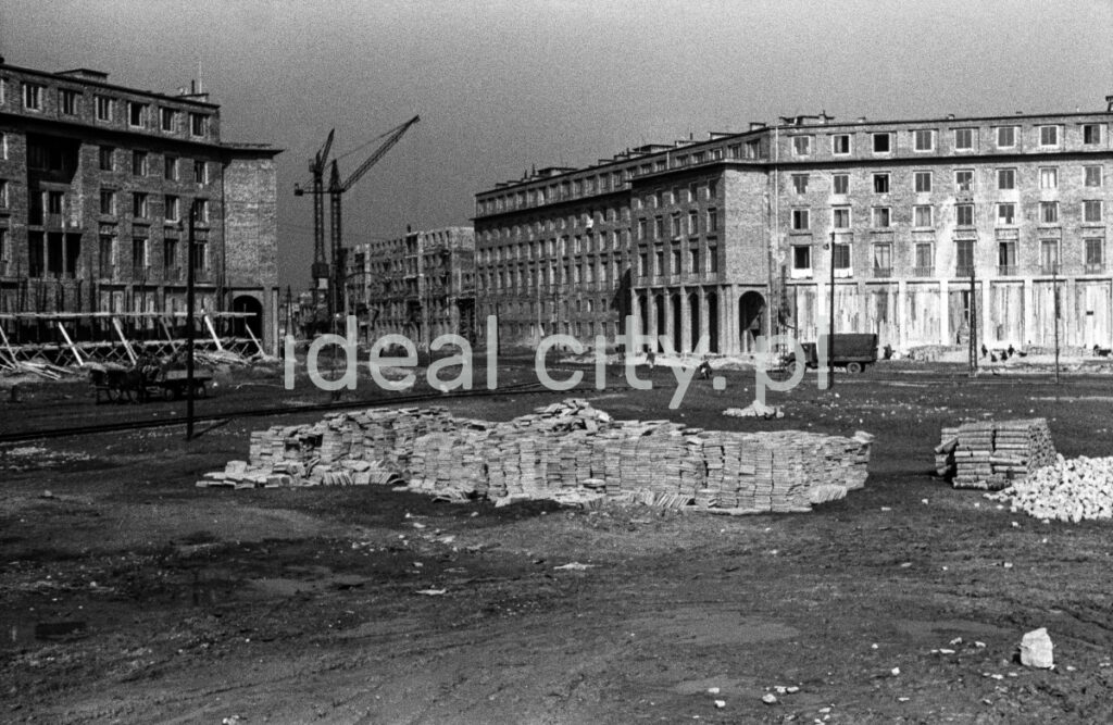 A view of a large square under construction, unfinished residential buildings in the background.