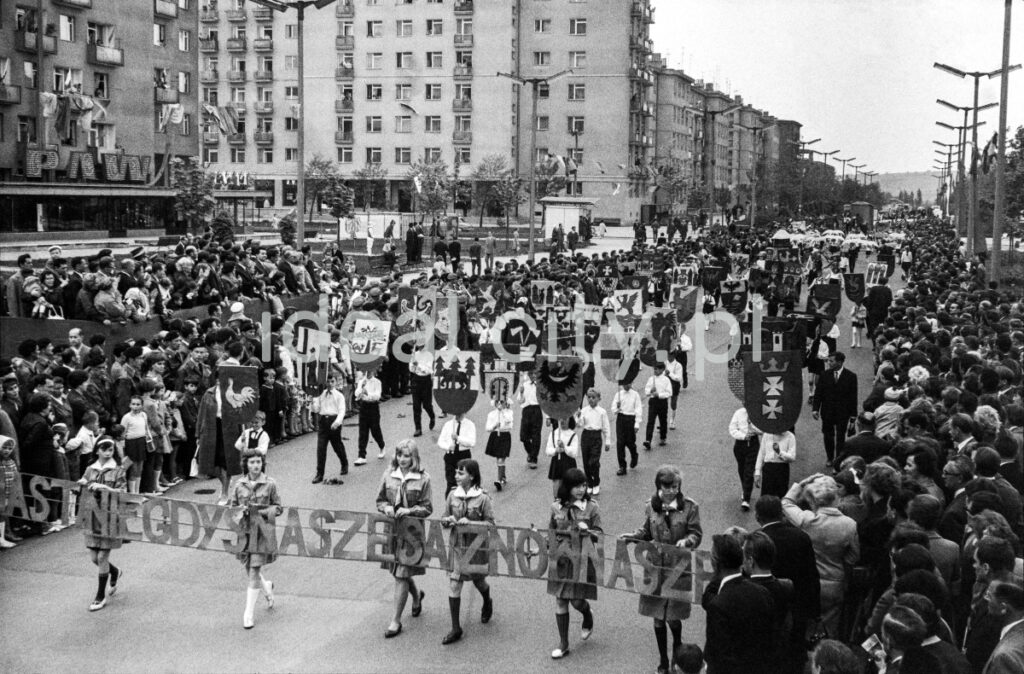 Children marching along a wide alley with the inscription: The cities that used to be ours are ours again.