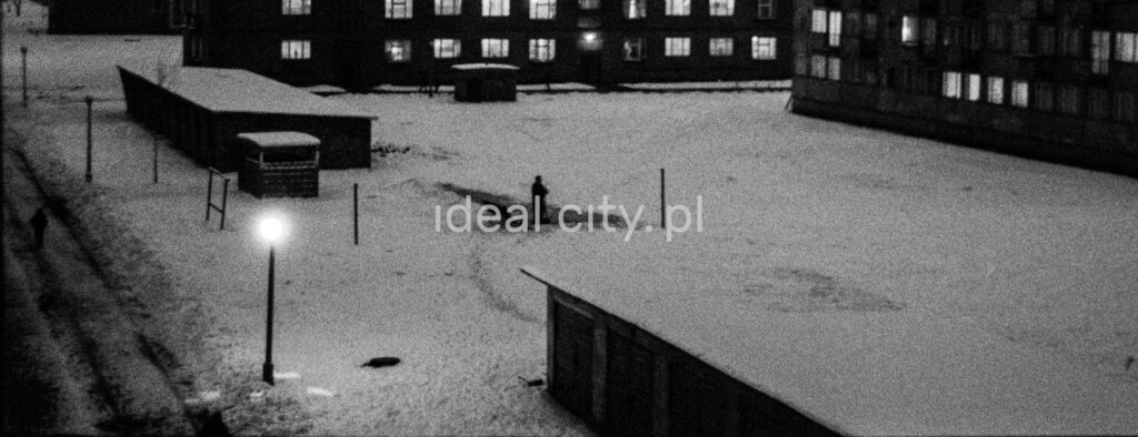 A night view from the window of the snow-covered yard between the blocks, a figure in a coat in the center.