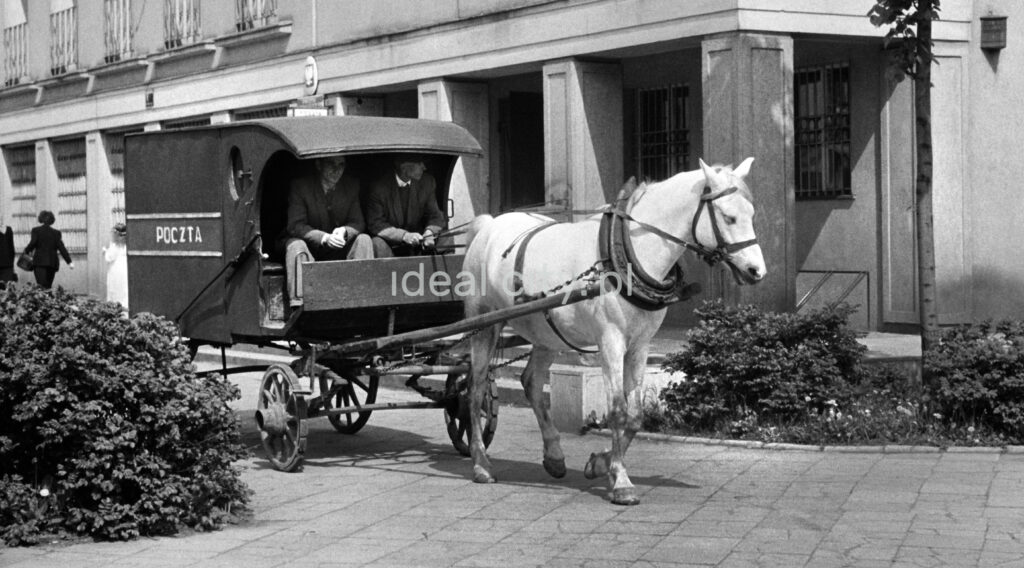 """A horse-drawn cart with the inscription """"post"""", drawn by a white horse, rides along the sidewalk next to the building."""