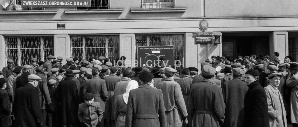 A crowd of men in coats and caps gathered in front of the office building.