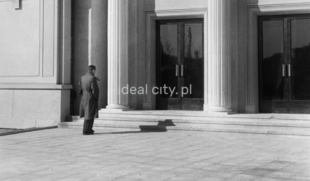 The man in the coat stands in front of the monumental entrance to the building.