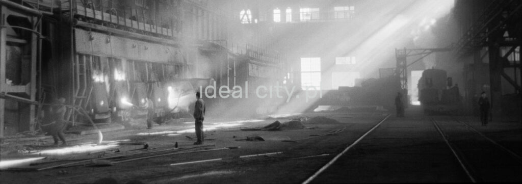 A man in the middle of a factory hall where the sun shines through fireflies.