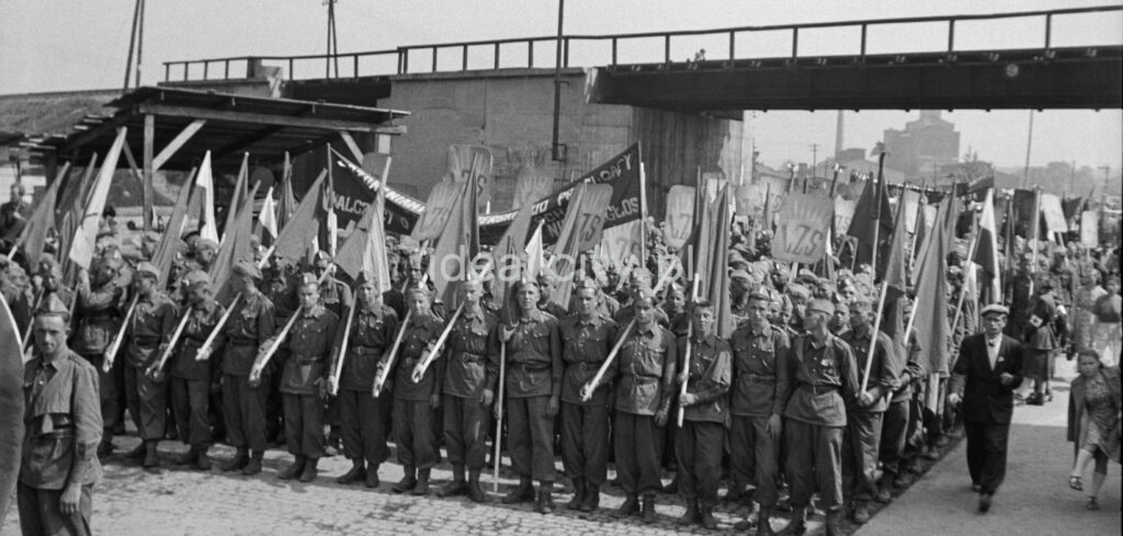 Young people dressed in uniforms march forward, holding flags in their hands.