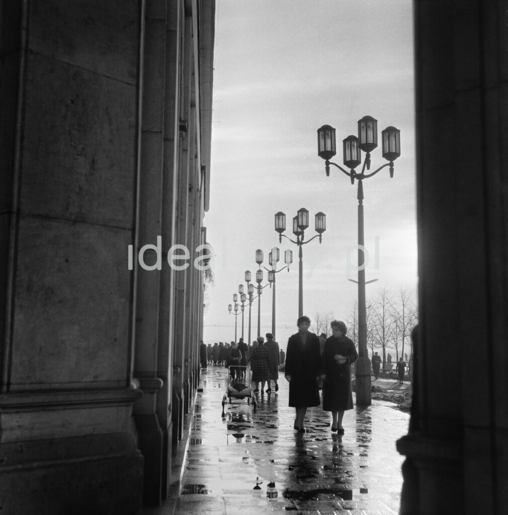 Pedestrian traffic on the promenade of the central square, next to the monumental arcades. Shot after the rain, against the sun.